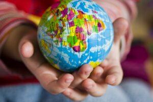 Child holding a ball that looks liek a world globe (Pixabay image)