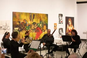 Hunter Wind quartet playing in a gallery space. Painting on the walls in background.